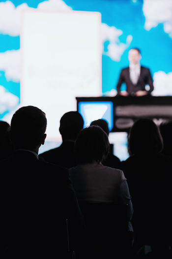 Presentation of a Speaker on the Stage Silhouette Speaker Stage Audience Presentation Media Press Conference Communication Public Event Technology Speech Meeting Seminar Politician Politics Entertainment Bussiness Government Corporate Live Leadership Campaign Correspondent Broadcast Corporate Business Business Person Watching Business Unrecognizable Person