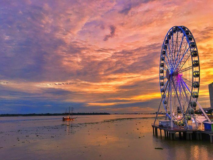 Ferris wheel at beach against sky during sunset
