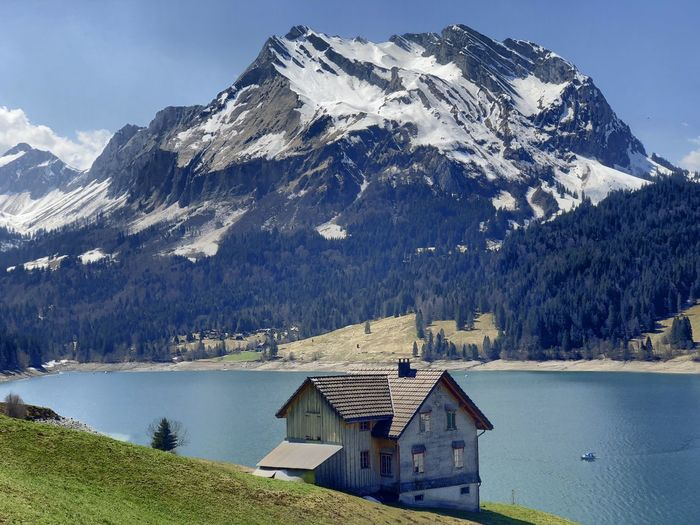 House on snowcapped mountain by lake against mountains