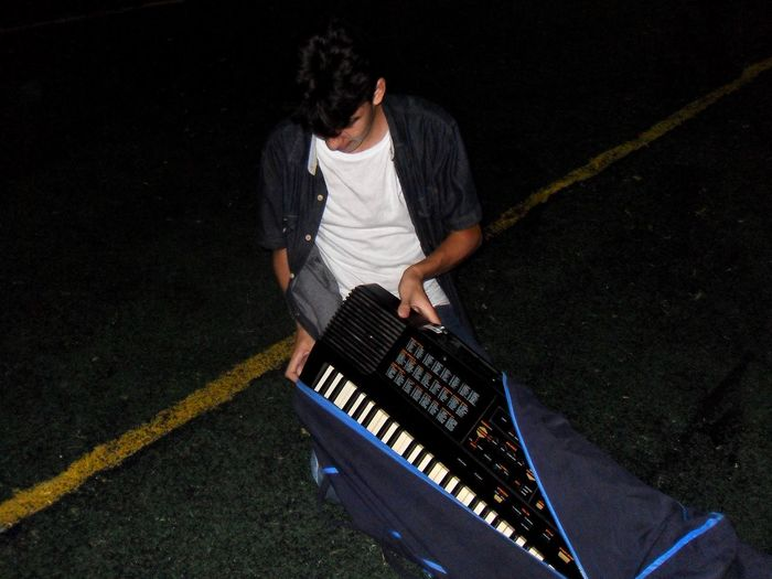 High angle view of man putting piano keyboard in cover on street at night