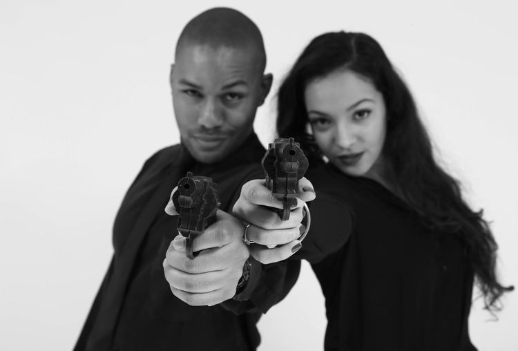 Portrait of fashionable gangster friends aiming gun at camera against white background