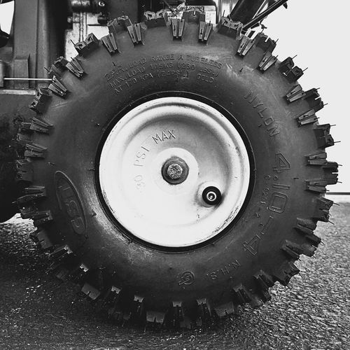 Knobby tire close-up in black and white. Metal Machine Part Machinery Close-up Wheel No People Tire Day Outdoors Black And White Photography Black And White Round Rubber Yard Machines Yard Work Snow Blower Knobby Letters Words Details