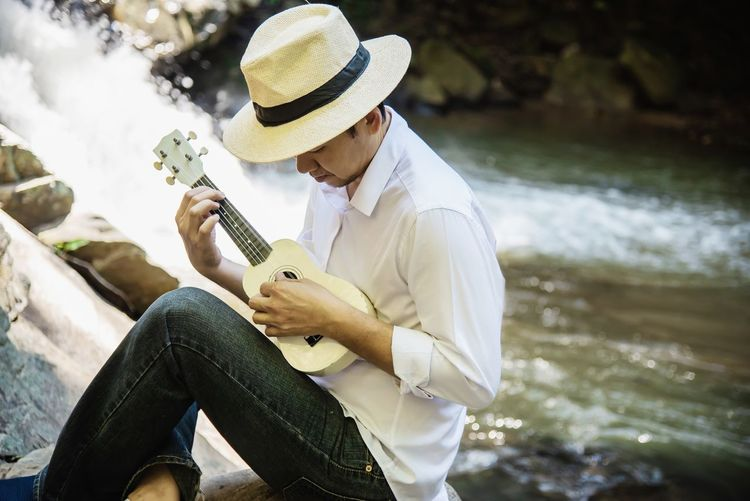 Man playing ukulele while sitting by river
