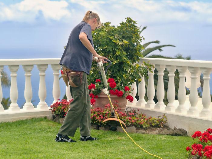 Full length of woman cutting grass in garden