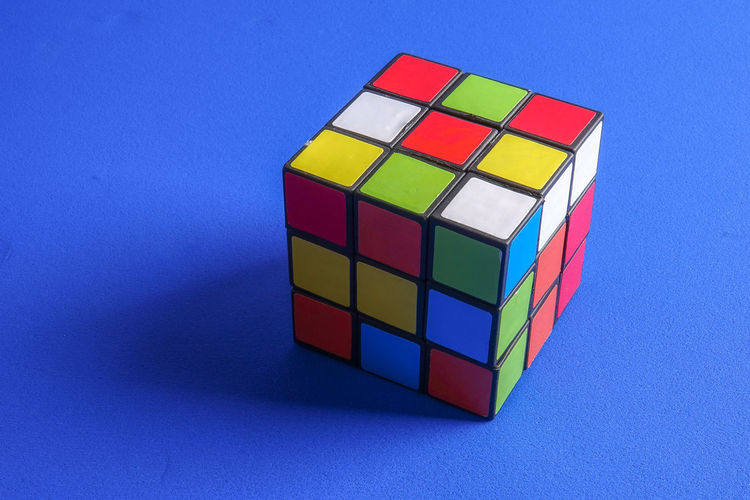 RUBIK'S CUBE , CREATIVITY TOY Creativity Rubik Cube Blue Blue Background Close-up Colored Background Copy Space Cube Shape Cut Out Design Geometric Shape High Angle View Indoors  Intelligence Multi Colored No People Rubik Shape Single Object Still Life Studio Shot Table Toy Toy Block