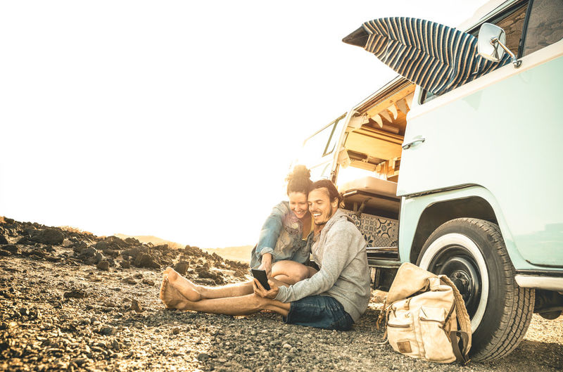 Hipster couple traveling together on oldtimer mini van transport - Travel lifestyle concept with indie people on minivan adventure trip having fun with mobile smart phone - Warm desaturated filter Surf Surfboard Surfers Couple Love Travel Van Mini Van Minivan Beach Relaxing Camping Roadtrip Trip Car Using Phone Selfie Mobile Phone Smartphone Friends Hippie Influencer Blogger Wanderlust Campervan