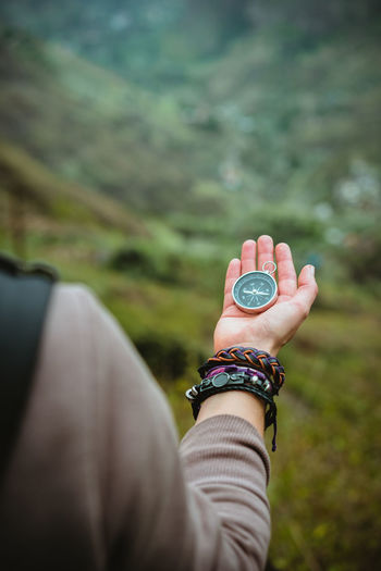 Midsection Of Woman Holding Navigational Compass On Mountain