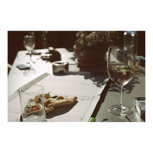 Wineglass by pizza box on table