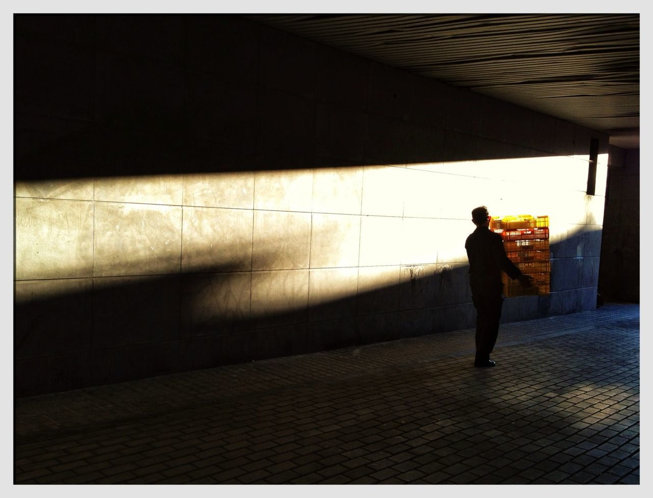 Silhouette man carrying crate in tunnel