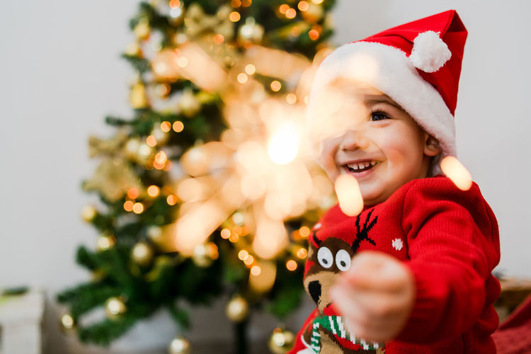 Christmas Celebration Tree Holiday Childhood Child Portrait christmas tree Decoration One Person Smiling Hat Christmas Decoration Happiness Santa Hat Holiday - Event Front View Cute Innocence Christmas Ornament