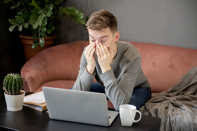 Young frustrated man sitting on sofa at home