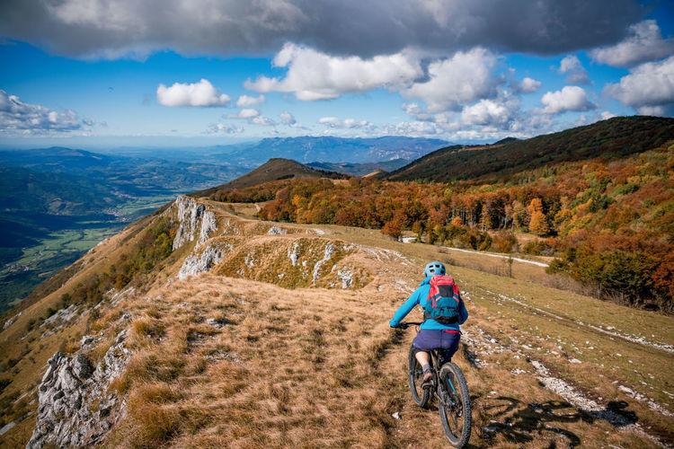 Woman mountain biking on footpath near ridge on mount nanos above vipava, slovenia.