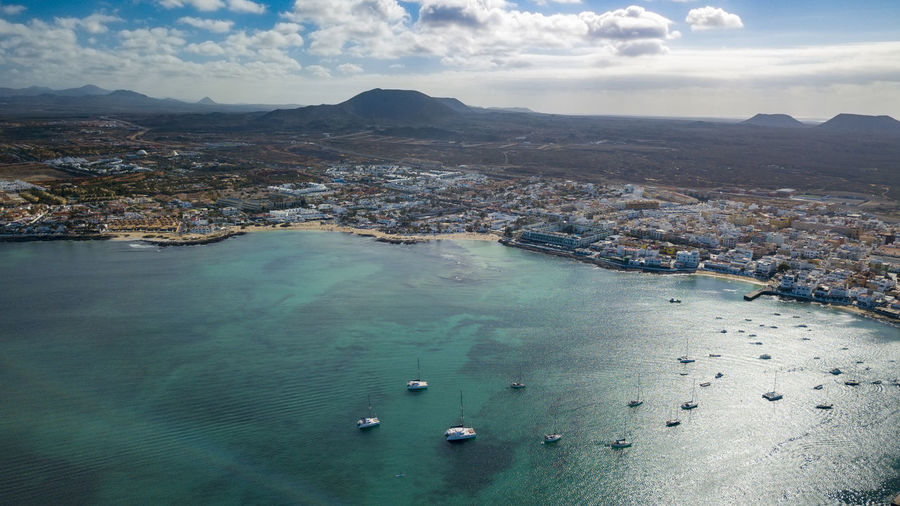aerial view of corralejo fuerteventura Aerial View Architecture Bay Beauty In Nature Building Exterior Built Structure Cloud - Sky Day High Angle View Mountain Nature Nautical Vessel No People Outdoors Scenics - Nature Sea Sky Tranquil Scene Transportation Water Waterfront