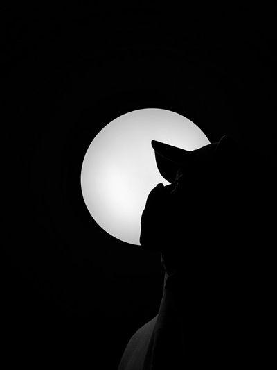Close-up portrait of silhouette man against black background