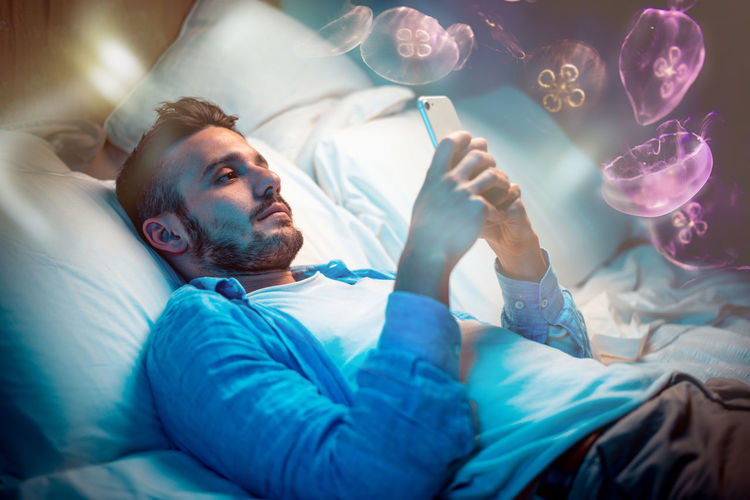 Double exposure of man using phone on bed and jellyfishes in water
