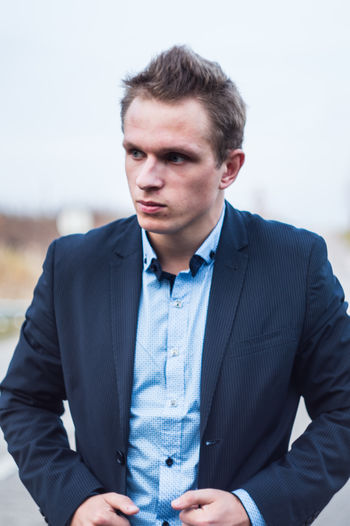 Man looking away while wearing suit against sky