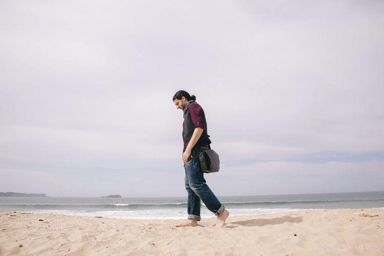 Full length of young man on beach against sky