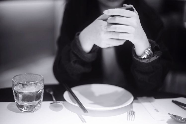 Midsection Of Woman Holding Mobile Phone While Sitting At Table