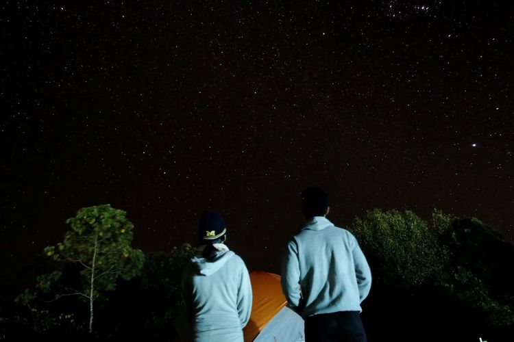 Rear view of friends looking at star field against sky during night