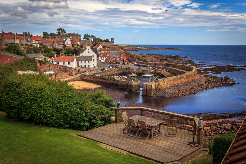 Looking across Crail Harbour Blue Sea Harbour View Seaside Village Bushes Clouds And Sky Garden Garden Table And Chairs No People Sea And Sky Stone Walls
