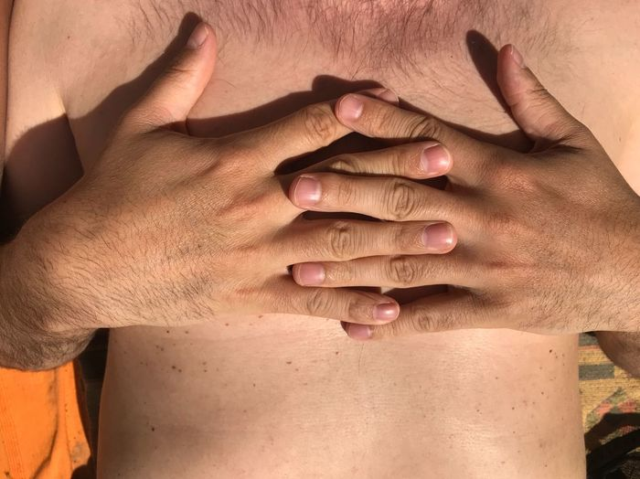 Midsection of shirtless man in sunny day