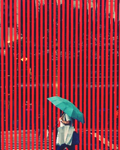 Woman with umbrella walking by wall