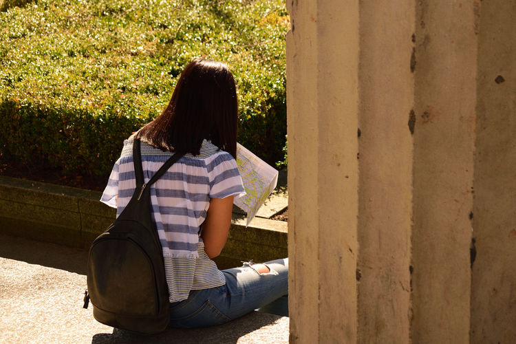 Rear View Of Woman With Backpack And Map Sitting Outdoors