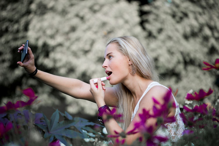 Side view of young woman applying lipstick at park