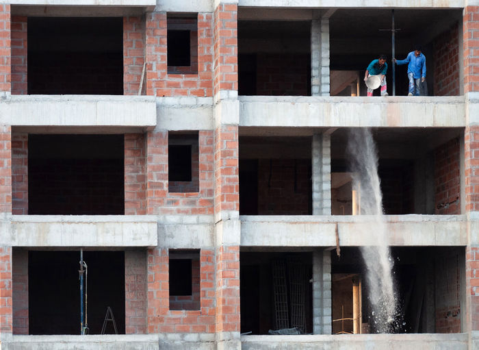 Rear view of men working at construction site