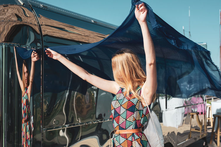 Woman holding blue scarf standing against bus