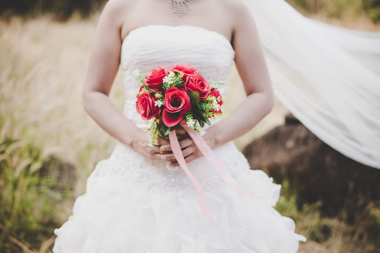 Midsection Of Bride Holding Rose Bouquet While Standing On Field