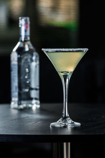 Alcohol Bar Counter Bottle Close-up Cocktail Container Drink Drinking Glass Focus On Foreground Food And Drink Freshness Glass Glass - Material Household Equipment Indoors  Martini Martini Glass No People Refreshment Still Life Table Transparent