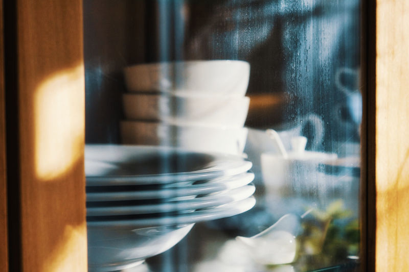 Close-up of crockery in cabinet at home