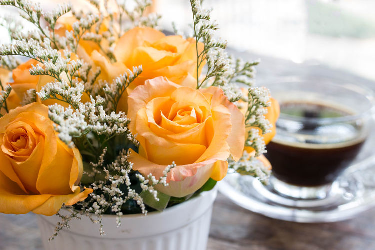 Close-Up Of Roses With Coffee On Table
