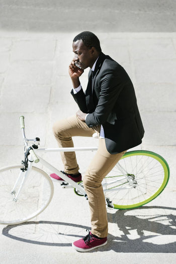 High angle view of businessman using smart phone while sitting on bicycle in city