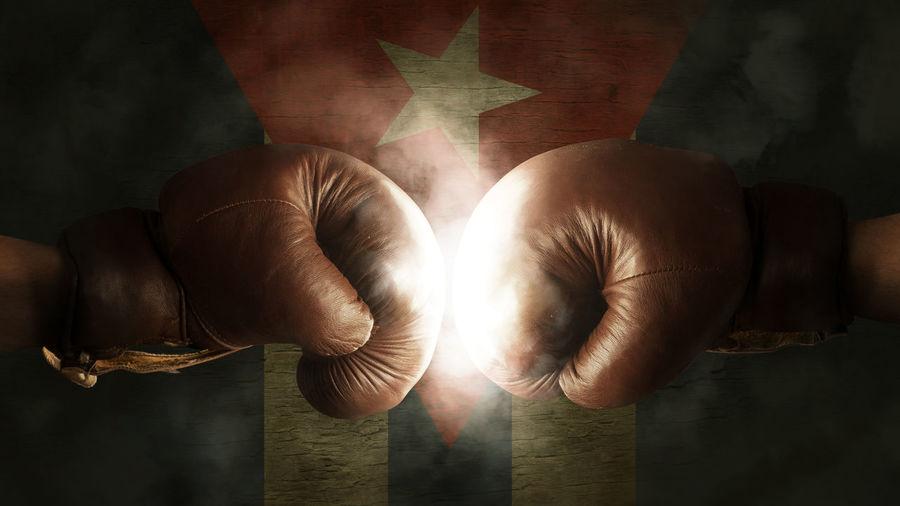 Cropped image of boxers fighting against illuminated cuban flag