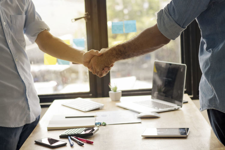 Midsection Of Business Colleagues Shaking Hands In Office