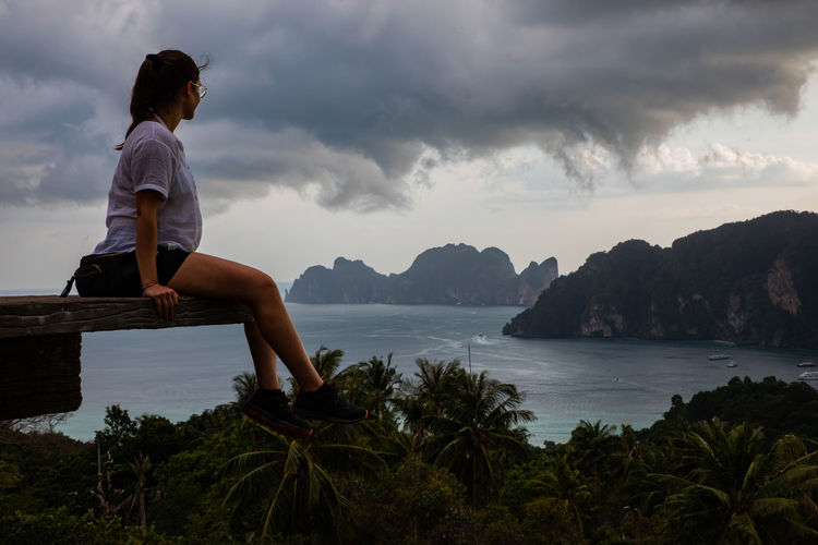 Side view of woman sitting at observation point with sea in background against sky