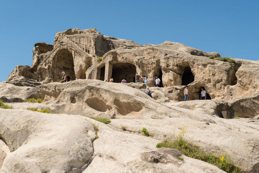 GEORGIA. UPLISTSIKHE CAVE TOWN - JUNE 13, 2017: Tourists walks through the cave city. Ancient Georgia Uplistsikhe Ancient Civilization Architecture Cave City Cave Town Clear Sky Hiking Leisure Activity Mountain People Real People