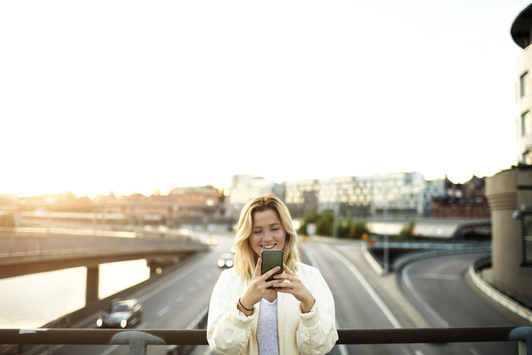 Young woman using mobile phone in city against sky