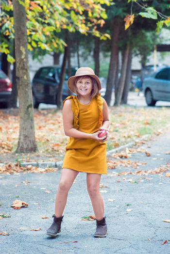Portrait of cheerful girl holding apple while standing on road
