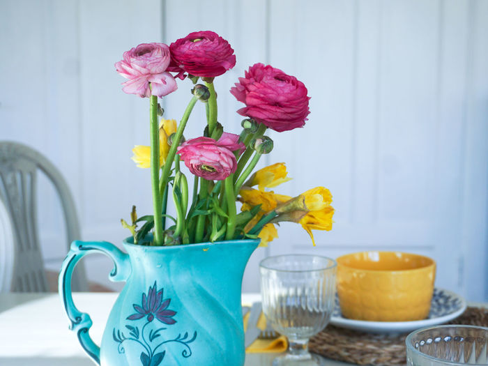 ranunculus flowers in a green vase Table White Background Table Setting Easter Ready Easter Sunday Yellow Yellow Flower Yellow Color Pink Pink Flower Spring Springtime Copy Space Flower Head Flower Bouquet Easter Vase Females Home Interior Springtime Flower Arrangement Plant Daffodil
