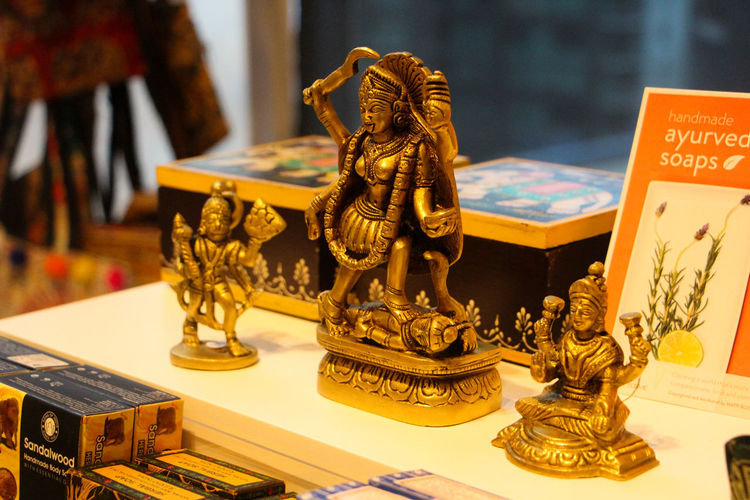 Art And Craft Representation Indoors  Human Representation Sculpture Focus On Foreground Creativity Statue Male Likeness No People Close-up Table Belief Gold Colored Craft Text Religion Antique Still Life