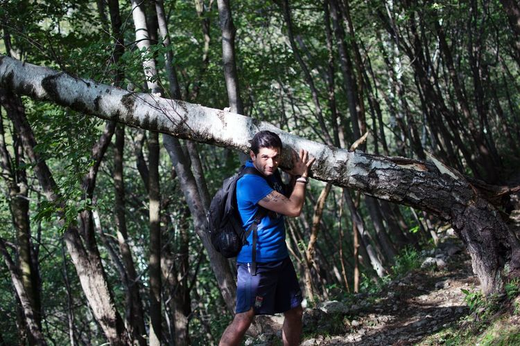 Young man standing on tree trunk in forest