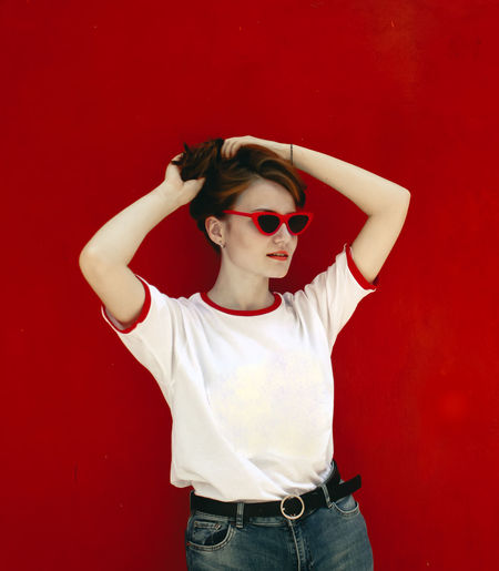 Portrait of boy wearing sunglasses against red wall