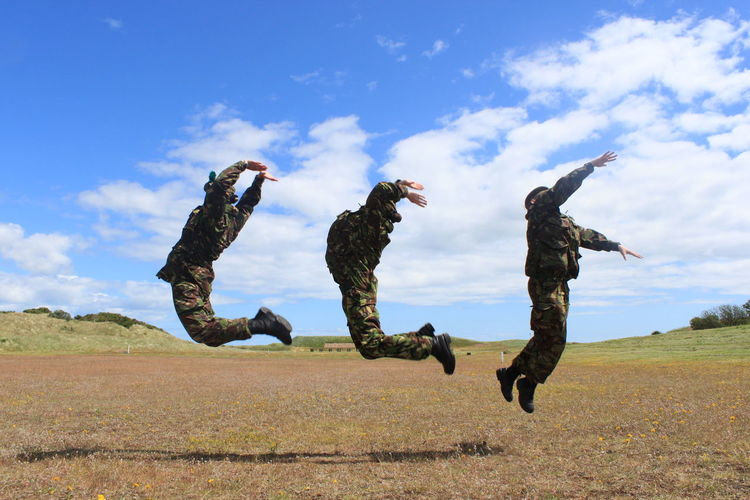 Full Length Of Soldiers In Mid-Air Over Field Against Sky