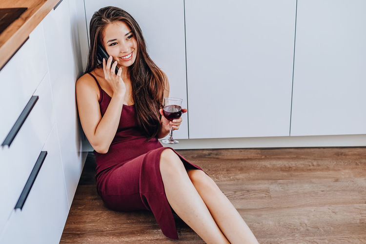 Young woman smiling while sitting on floor