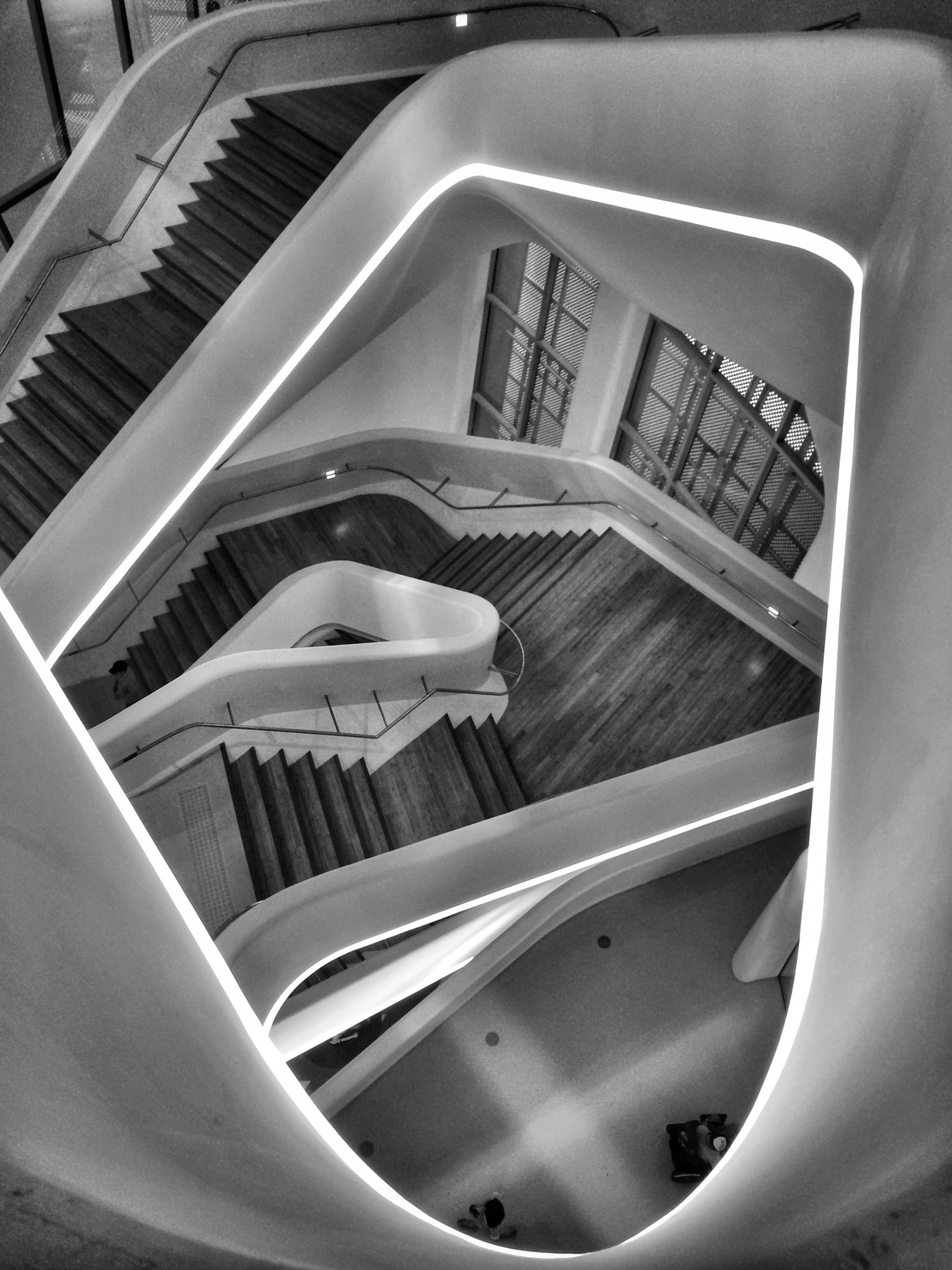 indoors, architecture, steps and staircases, built structure, staircase, railing, high angle view, steps, modern, building, building exterior, spiral staircase, no people, spiral, window, day, low angle view, absence, escalator, reflection