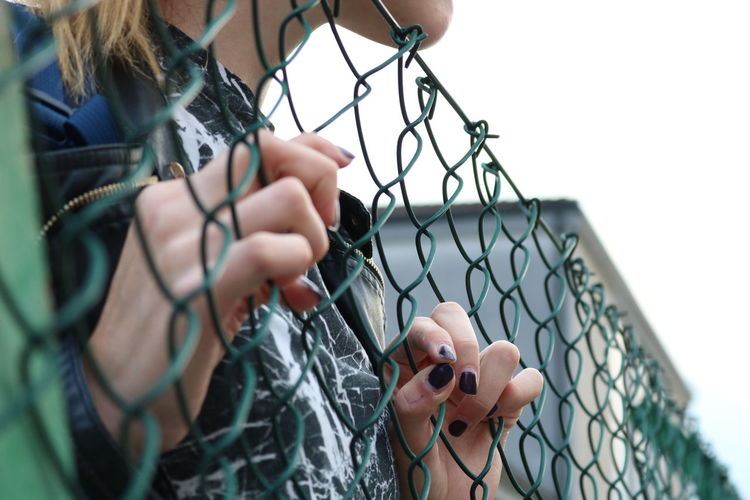 Close-up of woman holding chainlink fence
