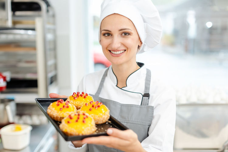 Portrait of young woman holding ice cream in kitchen